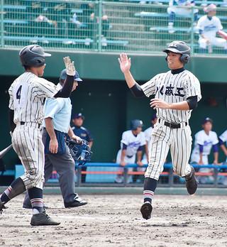 六回裏、前粟藏知弘の二塁打で生還して安里都哉(左)とハイタッチを交わす上地樹稀=9日午前、北谷公園野球場