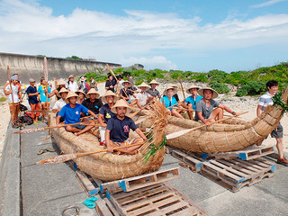 本番用の草舟とこぎ手たち。「早く挑戦したい」としけが収まるのを待っている=11日午後、比川カタブル浜