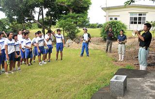 中学生を対象にした八重山農林高校の校外施設見学ツアーで、嵩田山荘について説明する與那城安昌君(右)=12日午前