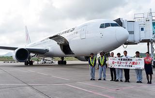 中型機(奥)の夏季運航を歓迎する横断幕で乗客を出迎えたJTAの空港職員(手前)=16日午後、南ぬ島石垣空港駐機場