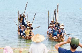 西表島に到着後、港で住民らの歓迎を受ける草舟のこぎ手ら=18日午後3時ごろ、西表島の白浜港