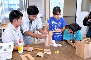 八重山特別支援学校の高等部の生徒たちが日ごろ学んでいる木工などの作業を小学生に教えた夏季体験教室=21日午後、同校