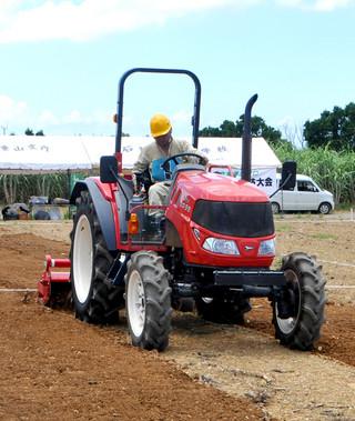 8年ぶりに開催された第6回八重山地区トラクター耕競技大会。競技者の横では審査員が安全な手順で作業しているかなどを確認していた=9日午後、石垣市平得