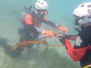 垂直素潜り結索を行う水難救助隊(右)と機動救難士(左)=19日午前、南ぬ浜町ビーチ(石垣航空基地提供)