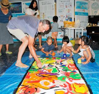 アート作品をつくるワークショップで演出家・美術家のダリオ・モレッティさん(左)と絵を描く子どもたち=27日午前、石垣港離島ターミナル内のとぅもーるネットセンター石垣