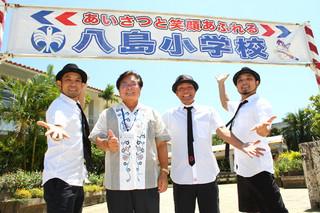 ライブをPRする左から崎枝亮作さん、宮良永秀校長、崎枝大樹さん、崎枝将人さん=30日午後、八島小学校校門