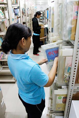 本を選定するみやら保育園の保育士ら=8月25日、市立図書館2階書庫