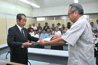 竹富町長選挙で初当選を果たし、当選証書を受け取る西大舛髙旬氏(左)=1日午後、竹富町役場2階の委員会室