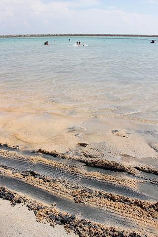 7月から期間限定で供用開始された人工ビーチ。干潮になると、波打ち際でもヘドロが確認される=4日午後、南ぬ浜町