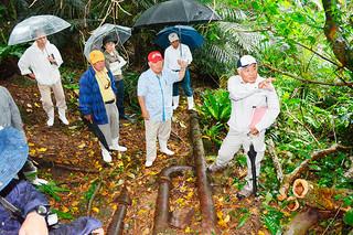 旧大浜町の浄水場施設(仮称)の当時の配水管について、松島昭司委員(右)から説明を受ける市文化財審議会の委員たち=9日午後、石垣市宮良