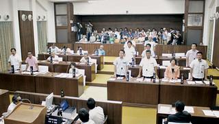 多くの傍聴人が見守る中、石垣島への自衛隊配備を求める決議に起立して賛成する与党11人=16日午前、本会場