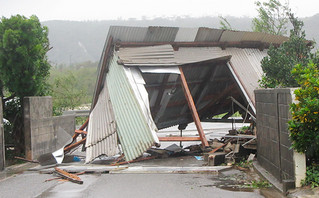 トタンぶきの倉庫が強風にあおられ、道路をふさぐ=17日午後、祖納(田頭政英通信員撮影)