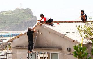 屋根の一部が飛ばされた北組爬龍船保管庫。漁業者らが修復に当たる=18日午後、久部良