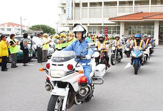 白バイを先頭に車両パレードに向かう警察官や市民ボランティアら=21日夕、八重山警察署玄関前