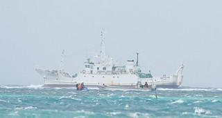 座礁した漁船(奥)の乗組員を水上バイクに乗せて琉球水難救済会八重山救難所の漁船に運ぶ市消防職員(手前)=27日午後2時36分、市内川平