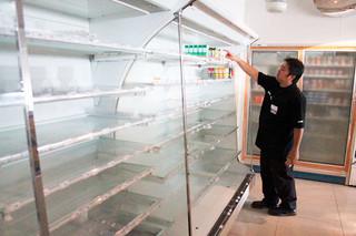 停電を受け、弁当などがくされないよう商品を移動させる店員=6日午前9時50分ごろ、ファミリーマート石垣シード店