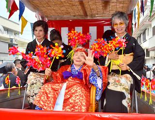 カジマヤー祝いで盛大な祝福を受けた花原マツルさん(中央)=9日午前、西表大原