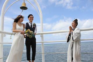 セレモニー後、神司の荻堂久子さん(右)から祝福を受ける小田寛・菜美さん夫妻=24日午前、フサキリゾートヴィレッジ