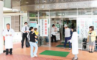 チラシを配布して未納診療費への理解を求める同病院の職員ら=1日午前、八重山病院玄関