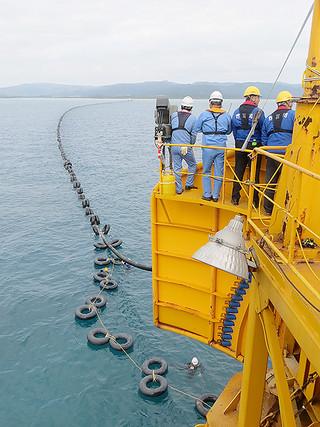 サルベージ船から流していく送水管。陸揚げのためチューブを取り付けて浮かせている=5日午前(竹富町水道課提供)