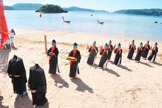 国の重要無形民俗文化財に指定されている「節祭」。祖納で厳かに奉納されたアンガー行列。海上には「まるま盆山」も見える=14日午後、祖納の前泊海岸