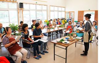 ハーブ講習会で、ハーブ指導者養成校・石垣島ハーブスクール代表の嵩西洋子氏(右)からハーブの活用法を学ぶ人たち=16日午後、伊原間公民館