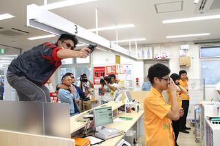 強盗対策模擬訓練で銃を突きつける犯人役の警察官。郵便局職員が強盗発生時の対応を確認した=17日夕方、石垣新栄郵便局