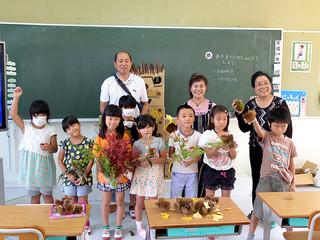 清水久雄さん(後列左)と平良八重子さん(同中)、與那國光子さん(同右)から贈られた「秋の自然」を前にする竹富小中学校の児童ら=15日同校