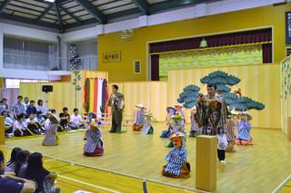 狂言「茸(くさびら)」で自作の面とかさに身を包んで出演し、キノコ役を堂々と演じる竹富小中学校の児童生徒たち=22日午後、同校体育館