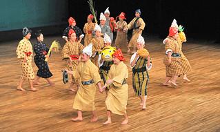 4年に1度開催している竹富町婦人連合会の芸能大会。各婦人会代表による恒例の演目「イイヤル節」では島々の多彩な特産品が登場した=26日午後、石垣市民会館大ホール