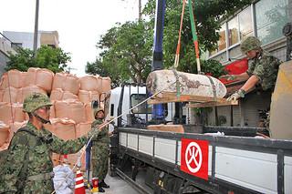 不発弾処理隊によって安全化処理され、トラックに運び込まれる250㌔爆弾=26日午後5時半ごろ、タウンパル山田前のゆいロード