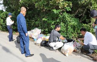 捨てられたごみ袋の中身を確認する市環境課の職員ら=5日午後、平得のトゥメスク御嶽