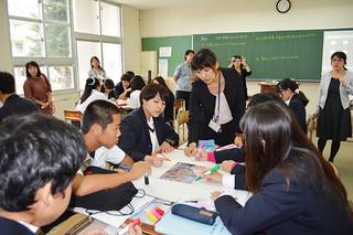 カンボジアに派遣された八重山商工高校の大城美由紀教諭(正面)の説明を受けながら、写真のタイトルを考える生徒たち=6日午後、同校
