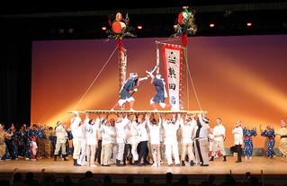 旗頭やツナヌミンも登場し、八重山の豊年祭が演じられた。=11月26日、板橋区立文化会館