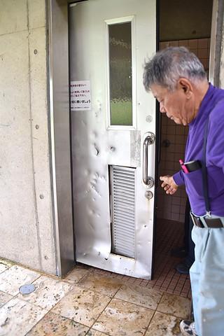 障がい者用ドアの下部が外れ、換気部分が何者かによって壊されているのを確認する市シルバー人材センターの会員=7日午後、崎原公園