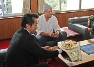 中山義隆市長にチャンピオンベルトをみせる廣虎選手(奥)=16日午後、市長室