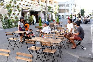 美崎町の通りをオープンカフェにして昼間のにぎわいを創出する社会実験で飲食を楽しむ人々=19日午後、石垣島ヴィレッジ前の市道