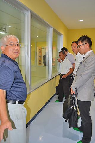 市立学校給食センターの宮良信世所長(左)から説明を受ける参加者たち=21日午後、同センター