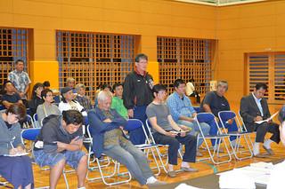 市教委の説明会に出席し、質問をぶつける地域住民ら。反発の声が相次いだ=22日夜、川原小体育館