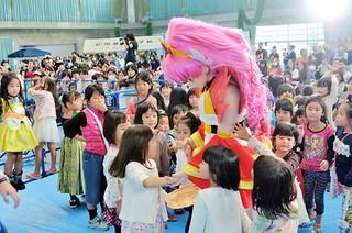 ゲストのプリンセスプリキュアのキュアフローラに群がる子どもたち=24日午後、石垣市中央運動公園屋内練習場