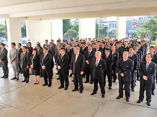 中山義隆市長のあいさつを聞く職員=4日午前、市役所玄関前ピロティ