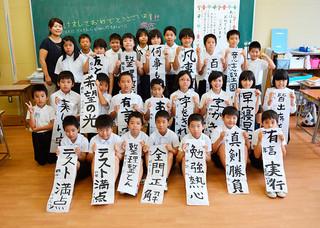 ことしの目標を書いた書き初めを手に笑顔をみせる登野城小学校4年1組の児童たち=6日午前、同校