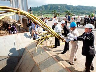 安全操業を祈願し、ケーンヤードにサトウキビの束を投入する関係者=6日午後、石垣島製糖
