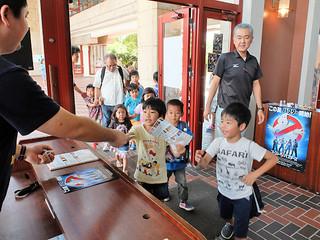 「ゴーストバスターズ」を観賞しようと最前列で待っていた子どもたち。チラシを受け取って会場へ=7日午後、市民会館大ホール