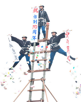 出初め式のはしご乗りで「無病息災」、「市制70周年」、「火の用心」(左から)を示す市消防団の女性団員=8日午後、市消防本部
