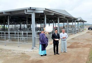 新牛舎の周囲で清めの儀式を行う関係者ら=12日午後、八重山肥育センター