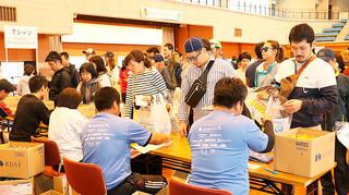 大会記念Tシャツを受け取る石垣島マラソンの参加者=21日午後、市総合体育館メインアリーナ