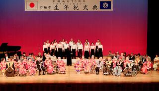 舞台上に勢ぞろいする97歳のカジマヤーを迎えたお年寄りら。市歌を斉唱する