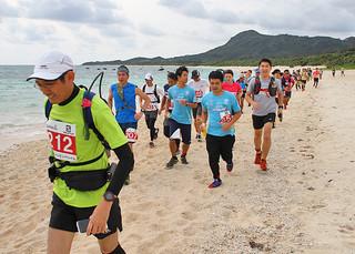 コースの8割がオーシャンビューとなる32㌔コースを走る選手ら=4日午前、伊原間海岸