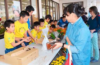 川原マーケットで、自分たちが育てた野菜や花の苗を販売する川原小学校の児童たち=5日午前、JAファーマーズマーケットやえやまゆらてぃく市場